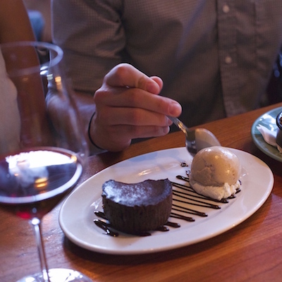 A couple enjoying chocolate cake with espresso gelato and a crumble at the bar
