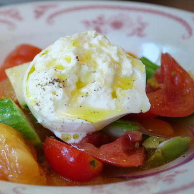 Heirloom tomatoes, with olives, cucumbers, basil, and onions - topped with burrata